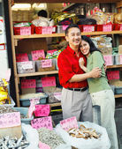 Young couple hugging in Asian market — Stock Photo