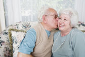 Senior man kissing senior woman on cheek — Stock Photo