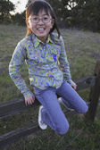 Young Asian girl sitting on a fence — Stock Photo