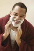 Africký muž použitím holicí krém čelit — Stock fotografie
