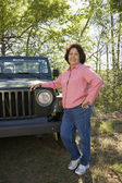 Senior woman leaning on jeep in woods — Stock Photo