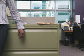 Midsection businessman leaning on filing cabinet — Stock Photo