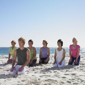 Group of women practicing yoga with instructor on beach — Stock Photo