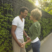 African couple smiling at each other outdoors — Stock Photo