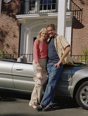 Middle-aged couple leaning on convertible — Stock Photo