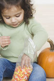 Little girl eating candy corn — Stock Photo