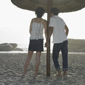 Hispanic couple holding hands on beach — Stock Photo