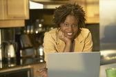 Jovem mulher africana na cozinha com laptop — Foto Stock