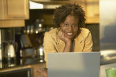 Young African woman in kitchen with laptop — Stok fotoğraf