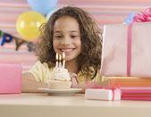 Giovane ragazza con cupcake e candele accese alla festa di compleanno — Foto Stock