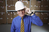 Businessman wearing hard hat and saluting in warehouse — Stock Photo