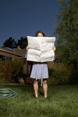 Man in robe reading newspaper in front yard — Stock Photo