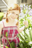 Girl holding flower in sunlit garden — Stock Photo