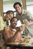 Multi-ethnic friends drinking at restaurant — Stock Photo