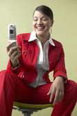 Woman smiling and looking at cell phone — Stock Photo