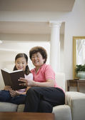 Asian grandmother and granddaughter reading — Stock Photo