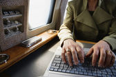Close up of businesswoman using laptop on private airplane — Stock Photo