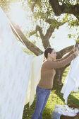 Hispanic woman hanging laundry on clothesline — Stock Photo