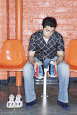 Man putting on bowling shoes — Stock Photo