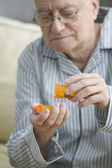 Older man shaking out pills into his hand — Stock Photo
