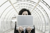 Businesswoman holding laptop in front of face — Stock Photo