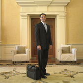 Businessman with briefcase in waiting area — Stock Photo