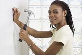 Afričanka zatloukání hřebíku do zdi — Stock fotografie