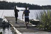 Young men carrying canoe away from lake — Stock Photo