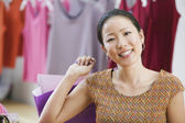Asian woman smiling and holding shopping bag — Stock Photo