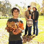 смешанные расы мальчик играет в осени листья — Стоковое фото