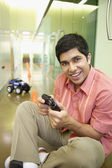 Businessman playing with an RC car in the hallway — Stock Photo