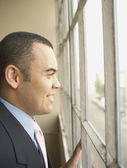 Businessman looking out window — Stock Photo