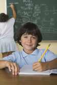 Boy writing in notebook while girl writes on blackboard in classroom — Stock Photo