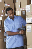 Male African warehouse worker scanning packages — Stock Photo