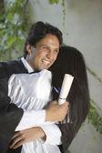 Afstuderen man en vrouw knuffelen elkaar — Stockfoto