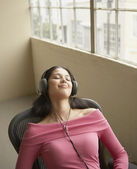 Businesswoman relaxing while listening to headphones — Stock Photo