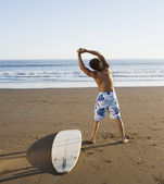 Hispanic man stretching next to surfboard — Stock Photo