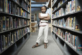 Girl standing in library — Photo