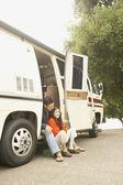 Couple sitting in doorway to recreational vehicle — Stock Photo