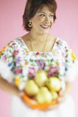 Middle-aged Hispanic woman with bowl of fruit — Stock Photo