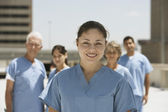 Hispanic female doctor smiling with co-workers in background — Stock Photo