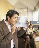 Businessman examining print of woman's sleeping face — Stock Photo