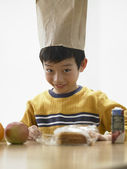 Young boy wearing lunch bag on his head — Stock Photo