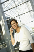 Businesswoman talking on cell phone in airport — Stock Photo