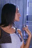 Hispanic woman looking through beaded curtain — Stock Photo