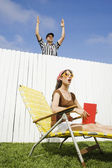 Hispanic referee making call over fence — Stock Photo