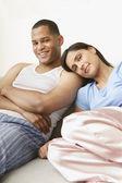 Couple wearing pajamas and smiling on sofa — Stock Photo