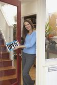 Portrait of woman hanging open sign on shop door — Stock Photo
