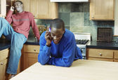 Brothers talking on cell phones in kitchen — Stock Photo