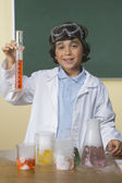 Young boy in science class holding beaker — Stock Photo